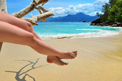 Sand beach, azure sea and woman legs Royalty Free Stock Image