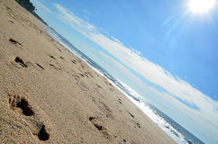 Sand beach and blue sky with sun by the sea Stock Photography