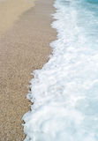 Sand beach and blue wave sea. With white foam Stock Images