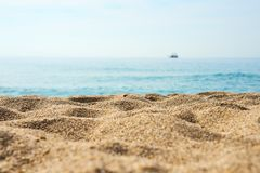 Sand on the beach close up with blurred sea, ship and waves on a background. Copy space royalty free stock photography