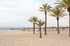 Sand beach deck chairs and pontoon Stock Image