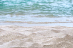Sand on the beach. The focus in on the sand, blurry sea wave as background Stock Images