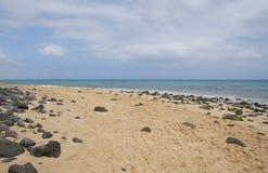 Sand beach with lava rocks in Fuerteventura Royalty Free Stock Image
