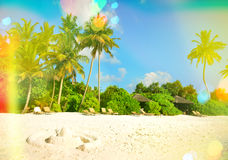 Sand beach with palm trees. Sunny blue sky with light leaks and. Tropical sand beach with palm trees and sunny blue sky. Vintage style toned picture with light Royalty Free Stock Photography