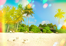 Sand beach with palm trees. Sunny blue sky with light leaks and. Tropical sand beach with palm trees and sunny blue sky. Vintage style toned picture with light Royalty Free Stock Photos