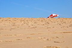 Sand beach and parasol over the blue sky Stock Photo