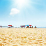 Sand beach with peoples and sun in clouds Stock Photography