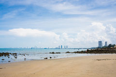 Sand beach and reef beach in ocean view with cityscape Royalty Free Stock Image