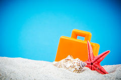 Sand beach with shells and suitcase Stock Photography