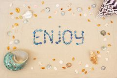 Sand on the beach in summer, the inscription enjoy from the shells on the sand. Flat lay. Top view royalty free stock photography