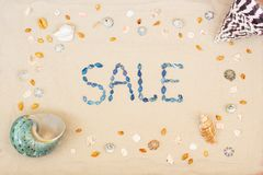 Sand on the beach in summer, the inscription sale from the shells on the sand. Flat lay. Top view royalty free stock image