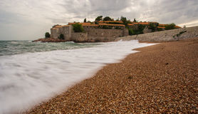Sand beach - Sveti stefan in background Royalty Free Stock Image