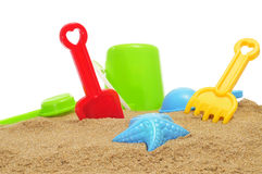 Sand / beach toys on the sand. Closeup of some beach toys, as a starfish-shaped sand mold, and shovels and rakes of different colors, on the sand of a beach or stock photos