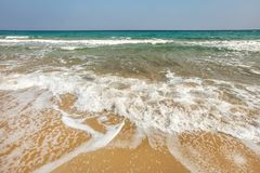 Sand on the beach wet from small waves; azure sea ad clear sky in background.  stock image