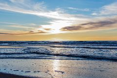 Free Sand Beach With Endless Horizon And Foamy Waves Under The Bright Sundown With Yellow Colors And Clouds Above The Sea Royalty Free Stock Photography - 148404527