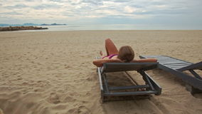 Sand Beach with Woman on Folding Chair Looks at Sea stock video footage