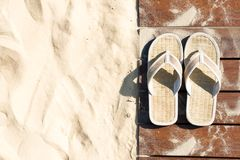 Sand and flip flops on boardwalk at sunny beach. Sand and beige flip flops. Pair of sandals on boardwalk. Walk on sand in bright sunny day, Leisure time at royalty free stock photography