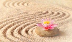 Sand, blommaliljan och brunnsortstenar i zen arbeta i trädgården arkivbild