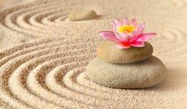 Sand, blommaliljan och brunnsortstenar i zen arbeta i trädgården royaltyfri bild