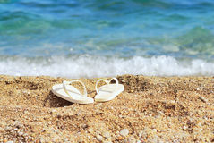 Sand blue sea and slippers. Focus on slippers Stock Image