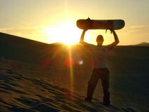 Sand boarding sunset. Over dunes Stock Photography