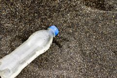 In the sand bottle of plastic sea Royalty Free Stock Photo