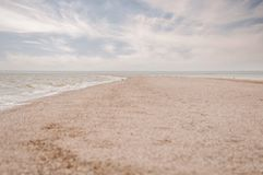 Sand braid going into Azov sea and cloudy sky stock photos
