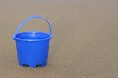 Sand bucket. Blue sand bucket on beach royalty free stock photo
