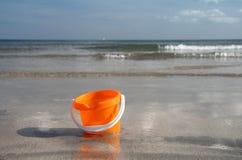 Sand bucket on the beach royalty free stock photo
