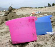 Sand Bucket Brigade. Two bright pastel water buckets sit in the foreground, as a sand sculpture of a man lurks in the background Stock Photography
