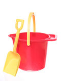 Sand bucket and shovel on white ground. Yellow handle up on red sand bucket with yellow shovel, isolated on white ground stock image