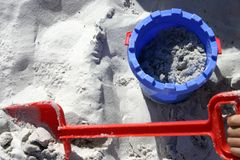 Sand Bucket and Spade. Blue and red, bucket and spade in sand at beach Royalty Free Stock Images