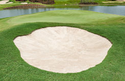 Sand bunker and clear lake on the beautiful golf course Royalty Free Stock Photo