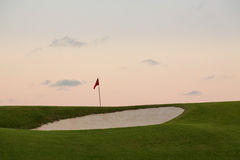 Sand bunker in front of golf green and flag Royalty Free Stock Image