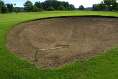Sand bunker on golf course. Closeup of newly raked sand bunker on golf course with fairway in background Royalty Free Stock Photo