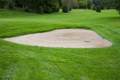 Sand bunker on golf course. Newly raked sand bunker on golf course with fairway in background Royalty Free Stock Photos