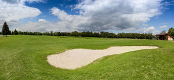 Sand bunker on golf course with perfect green grass Stock Image
