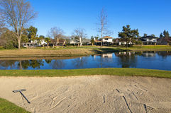 Sand bunker on the golf course with trees and pond Royalty Free Stock Photography
