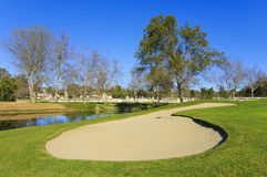 Sand bunker on the golf course with trees and pond Royalty Free Stock Images