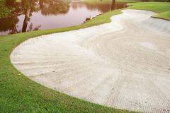 Sand bunker in green golf fairway. Royalty Free Stock Image
