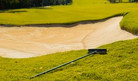 Sand Bunker Hazard and rake on Golf Course Fairway. In afternoon light royalty free stock photos