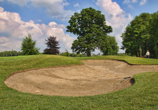 Sand bunker before reaching the hole. Vibrant sky Royalty Free Stock Photo
