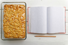 Sand cake with lemon-orange filling and notebook for recipes Royalty Free Stock Image