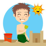 Sand Castle. Little boy sweating building a sandcastle on the beach with shovel and bucket on a hot sunny summer day Stock Images