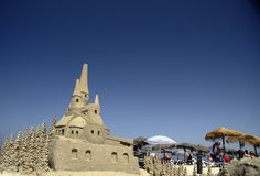 Sand castle. Big sand castle on beach, straw umbrellas, and tourists Stock Images
