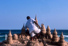 Sand Castle. Black man sculpturing a big sand castle on a beach of Rio de janeiro, Brazil Stock Images
