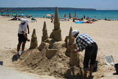 Two men build a sand castle on the beach on a Sunny day Royalty Free Stock Images
