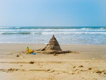 Sand castle, baby bucket and shovel by the sea. Lonely sand castle on the beach of the Indian Ocean stock image