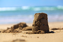 Sand castle on beach. Traditional sand castle on beach with sea in background Stock Photo