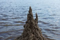 Sand castle on the beach against the water. Summer day royalty free stock photography
